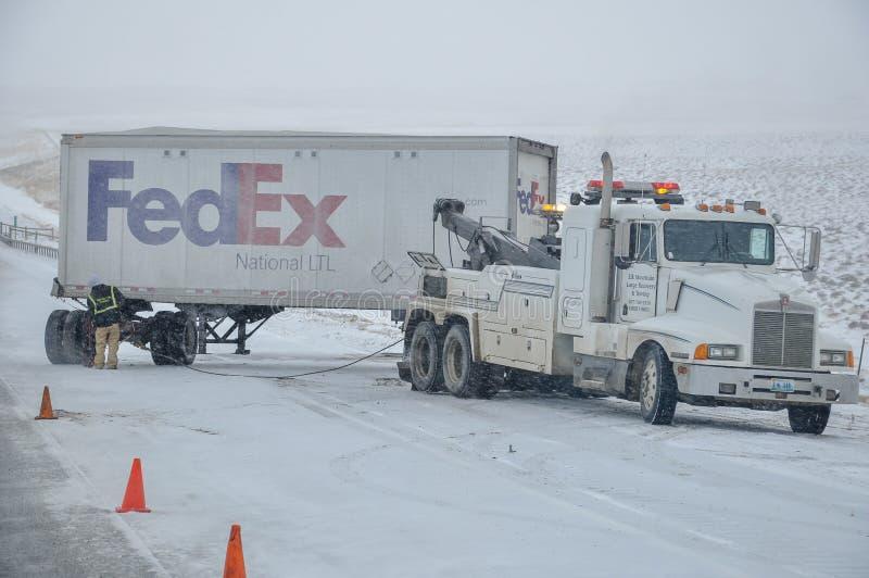 СЕВЕРНЫЙ PLATTE, НЕБРАСКА - 25-ое февраля 2010 - тележка отбуксировки получает готовым вытянуть трейлер Federal Express вне ледис стоковое изображение