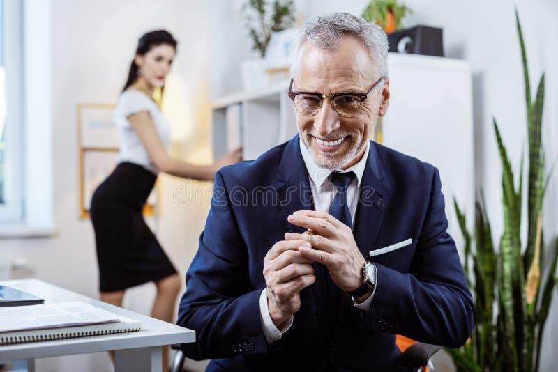 Седой старший человек с неприятной улыбкой извлекая его кольцо стоковые изображения rf