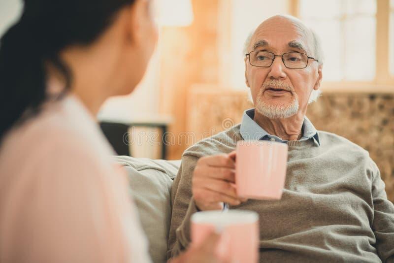 Седой человек с белой бородой и розовой чашкой отдыхая на софе стоковое фото rf