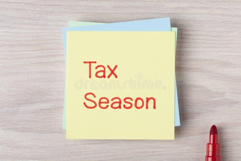 Сезон налога написанный на примечании стоковые изображения