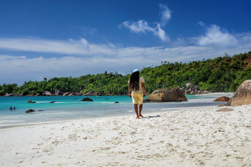 СЕЙШЕЛЬСКИЕ ОСТРОВЫ, PRASLIN - 3-ЬЕ АВГУСТА: Rasta идет вдоль пляжа Anse Лациа на острове Praslin 3-его августа 2015, Сейшельские стоковое фото rf