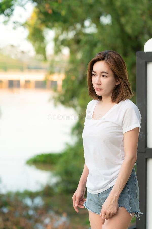 Сексуальная азиатская женщина в шортах голубых джинсов моды и белой футболке стоковое фото rf