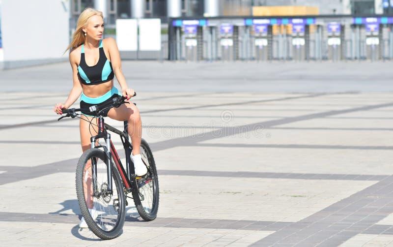 Сексуальная белокурая девушка в tracksuit ехать велосипед стоковое изображение