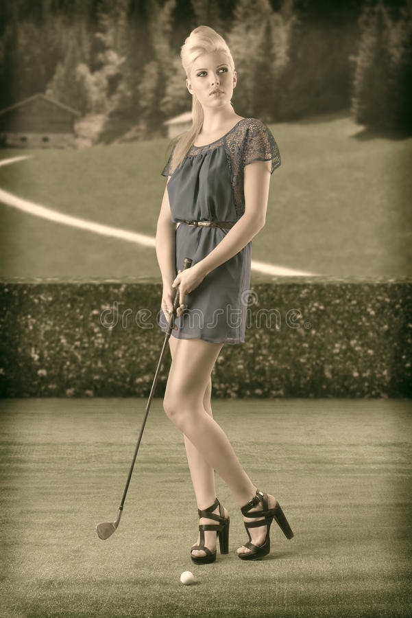 Сексуальная белокурая девушка оплачивает гольф, в типе сбора винограда стоковые фото