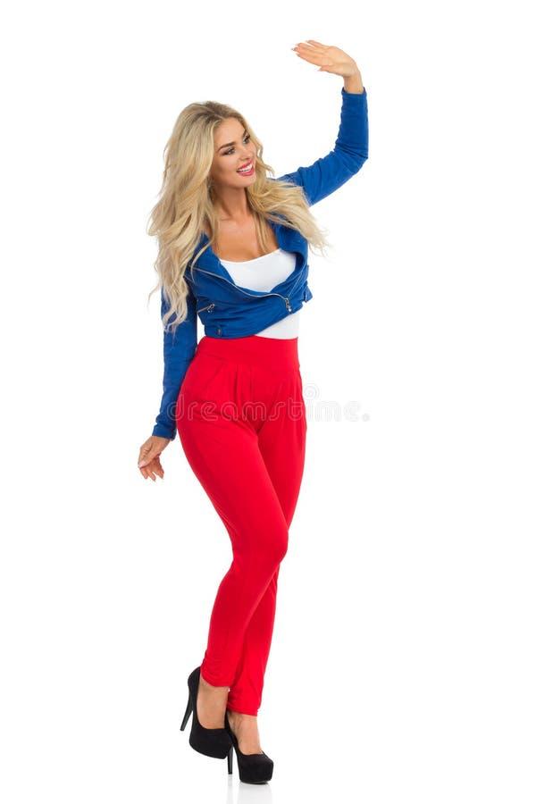 Сексуальная белокурая женщина в куртке, красных брюках и высоких пятках стоит и развевает стоковые фото