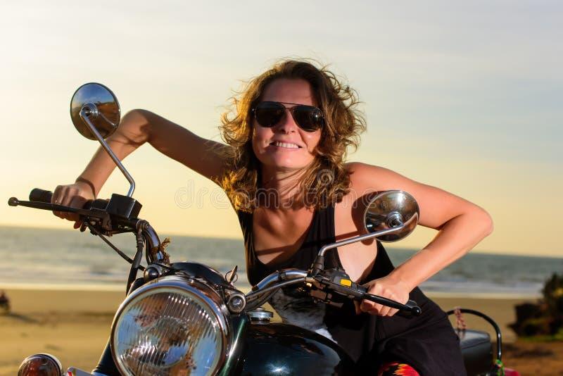 Сексуальная белокурая женщина в солнечных очках усмехаясь и гримасничая пока сидящ на мотоцикле Яркие эмоции на каникулах стоковое изображение rf