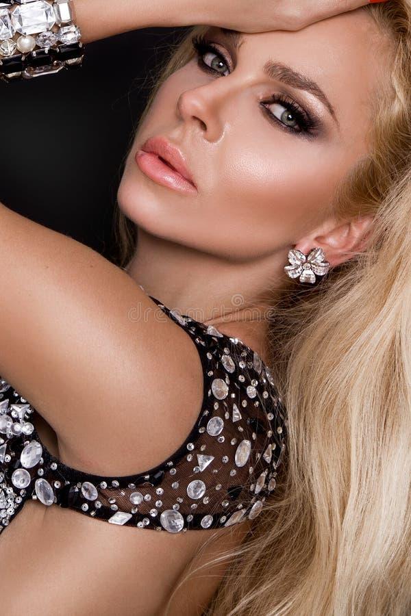 Сексуальная белокурая женщина при длинные волосы одетые в элегантных кристаллах одевает стоковая фотография
