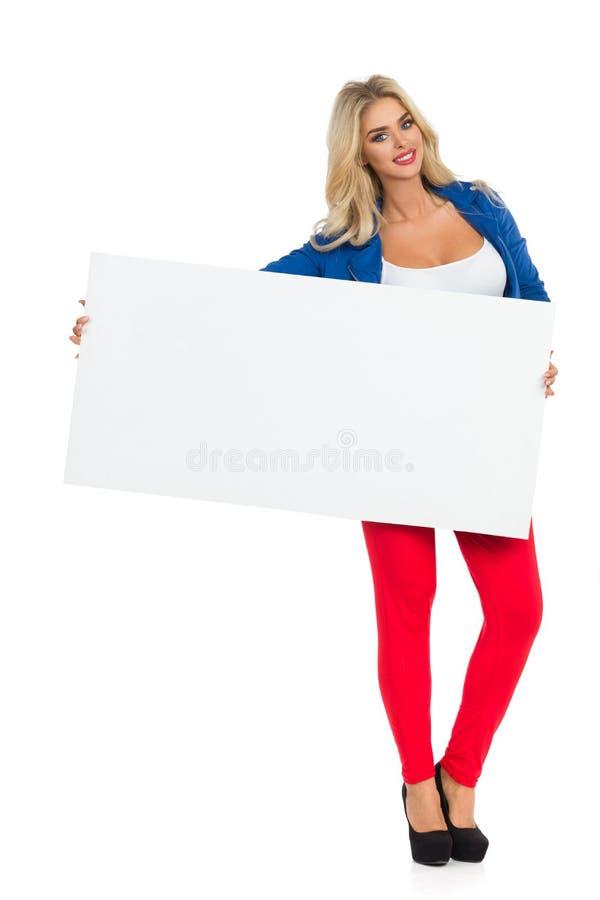 Сексуальная белокурая женщина стоящ и проводящ белый плакат стоковое изображение rf