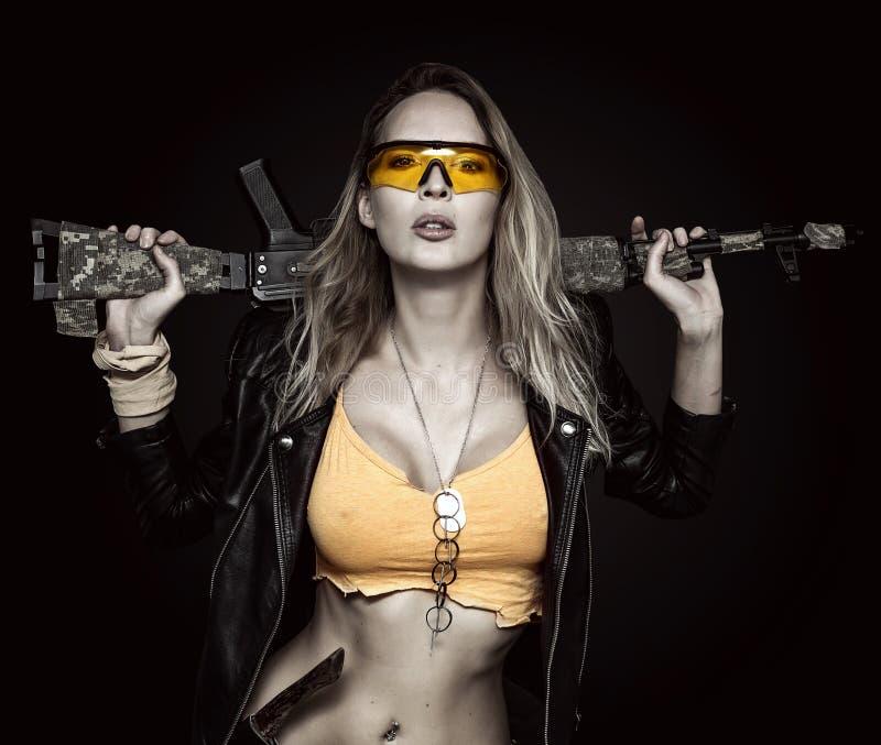 Сексуальная белокурая опасная женщина с автоматом стоковое фото rf
