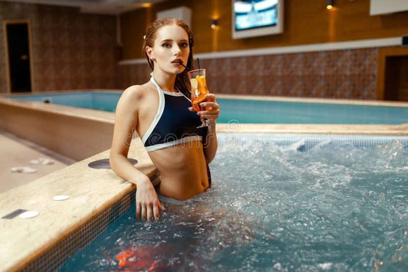 Сексуальная девушка выпивает коктейль плода на стороне бассейна стоковая фотография
