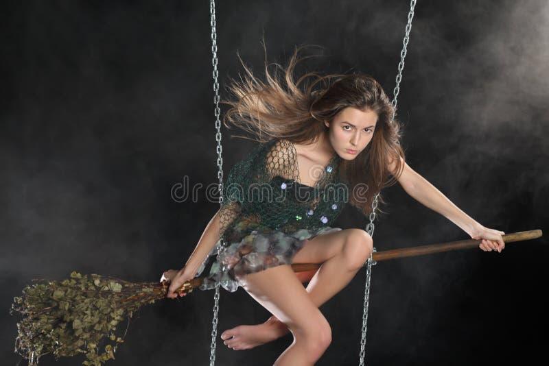 Сексуальная девушка в костюме ведьмы сидит на broomstick в дыме стоковая фотография rf