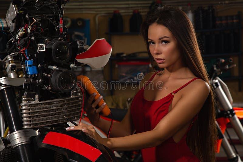 Сексуальная девушка ремонтируя мотоцикл стоковые изображения rf