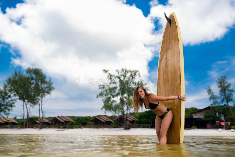 Сексуальная девушка стоя в воде с доской затвора стоковые фотографии rf
