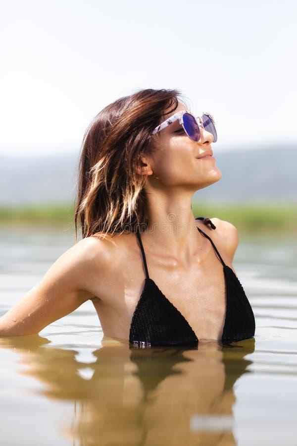 Сексуальная девушка с стеклами в воде стоковая фотография