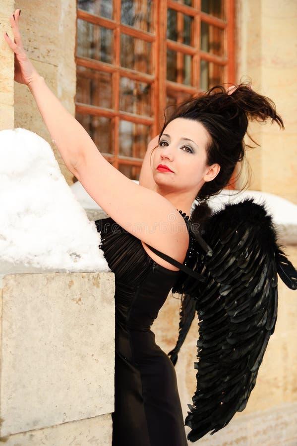 Сексуальная девушка с черными крыльями ангела в черном платье стоковое фото
