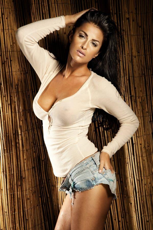 Сексуальная женщина брюнет представляя в белой рубашке и коротких джинсыах стоковая фотография rf