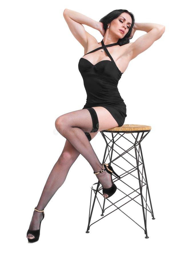 Сексуальная женщина в малом черном чулке платья и fishnet и высоко-накрененные черные ботинки на белой предпосылке стоковое фото
