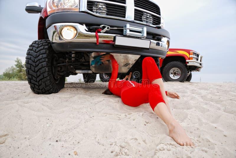 Сексуальная женщина ремонтируя красный виллис стоковое изображение