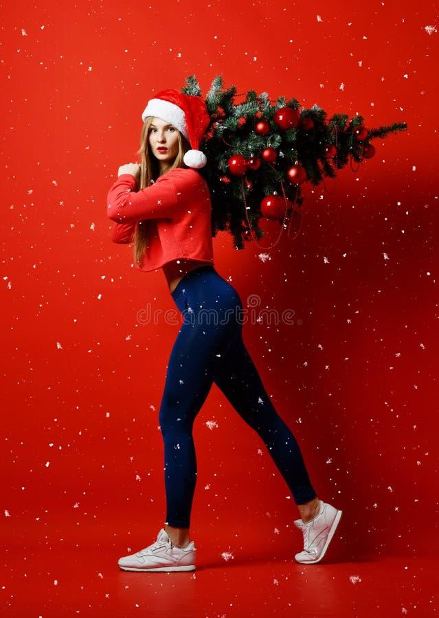 Сексуальная женщина спорта фитнеса рождества нося шляпу santa держа дерево xmas на ее плечах снежинки стоковые изображения