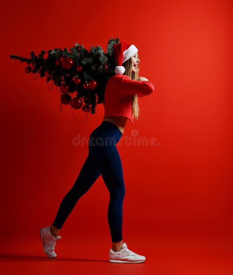 Сексуальная женщина спорта фитнеса рождества нося шляпу santa держа дерево xmas на ее плечах стоковые изображения