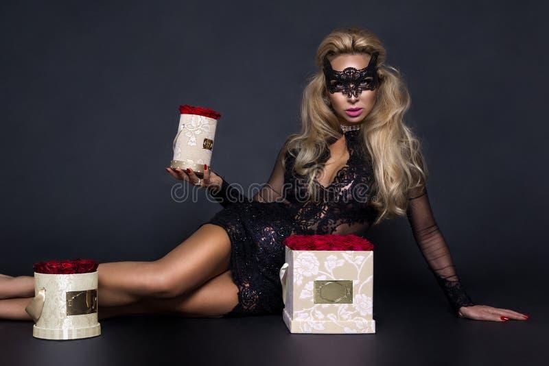 Сексуальная красивая белокурая модель в элегантном платье держа подарок, коробку цветка с розами Валентайн подарка s стоковая фотография rf