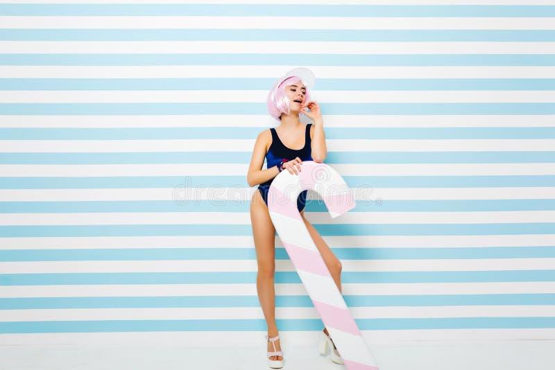 Сексуальная модная модель в bodysuit наслаждаясь летом на сине-белой striped предпосылке Нося стиль причесок пинка отрезка, пятки стоковое изображение rf