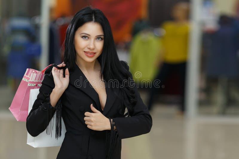 Сексуальная молодая женщина в черном костюме с хозяйственными сумками над предпосылкой мола стоковые фото