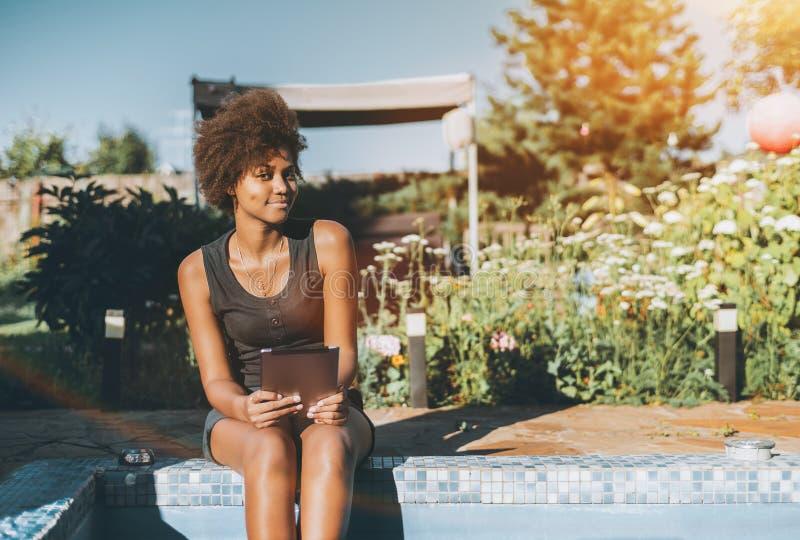 Сексуальная черная девушка в саде с бассейном стоковое фото rf