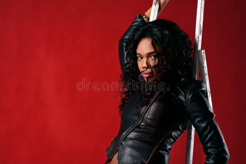 Сексуальная чернокожая женщина на красной предпосылке стоковое фото