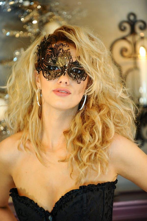 Сексуальная элегантная молодая дама нося черный корсет и венецианскую маску стоковое фото
