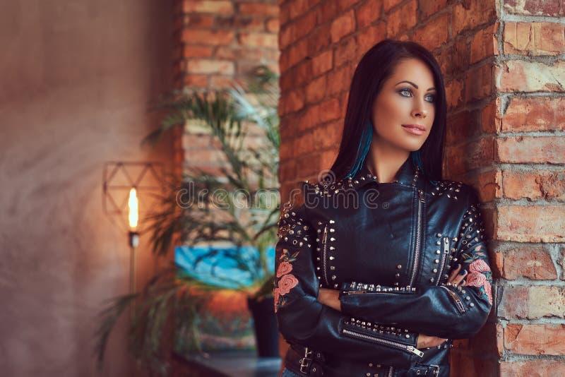Сексуальное чувственное брюнет представляя в стильной кожаной куртке и джинсах полагаясь против кирпичной стены стоковая фотография rf