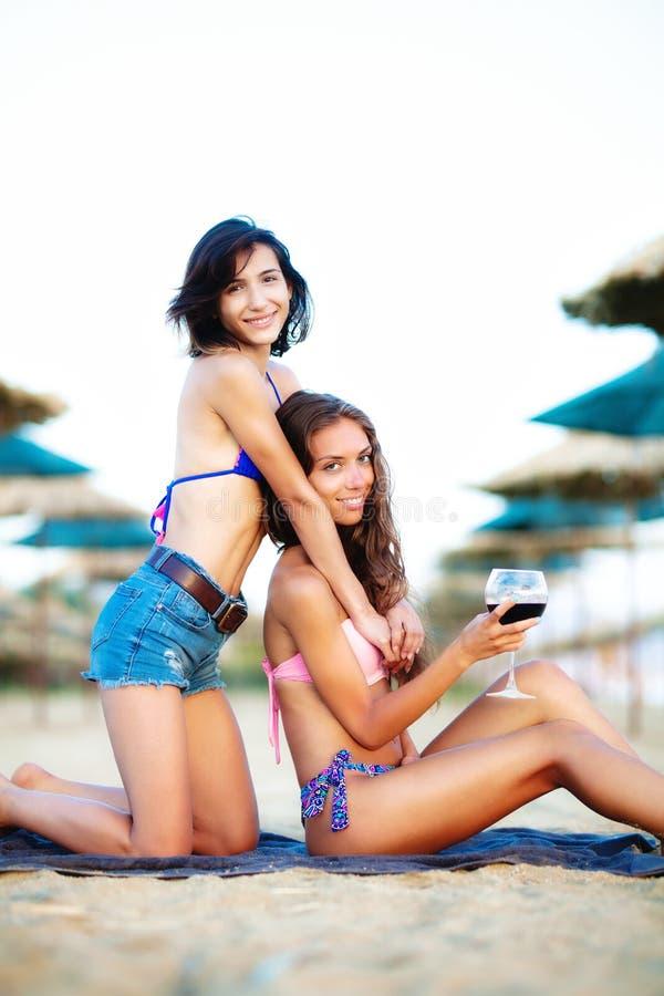 Сексуальные девушки имея вино и потеху на пляже стоковое фото rf