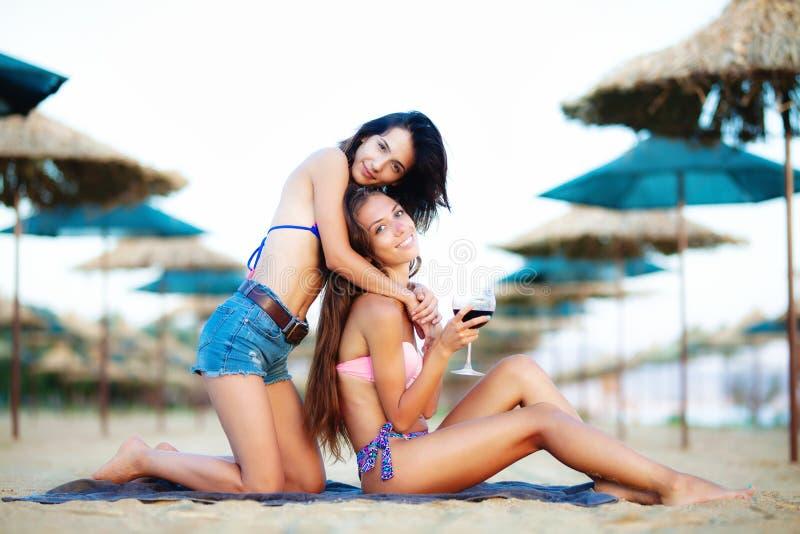 Сексуальные девушки имея вино и потеху на пляже стоковые изображения rf
