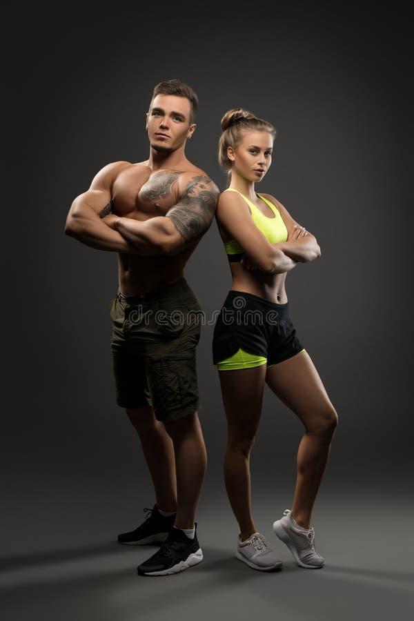 Сексуальные молодые пары фитнеса сняли на серой предпосылке стоковое фото