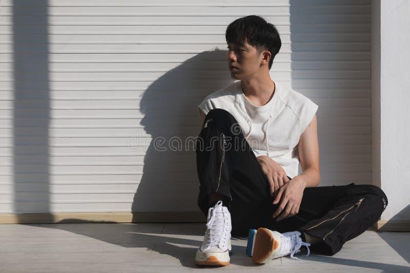 Сексуальный азиатский модельный человек сидя и смотря на левая сторона стоковая фотография