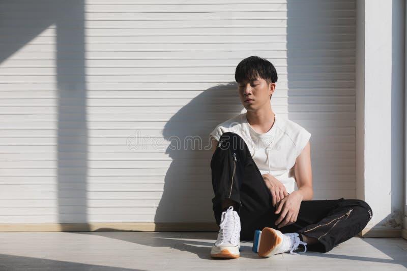 Сексуальный азиатский модельный человек сидя и смотря на левая сторона стоковая фотография rf