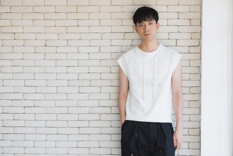 Сексуальный азиатский модельный человек стоя и представляя стоковая фотография