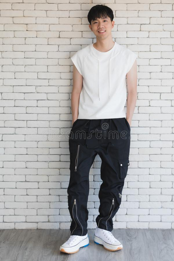 Сексуальный азиатский модельный человек стоя и представляя стоковое изображение rf