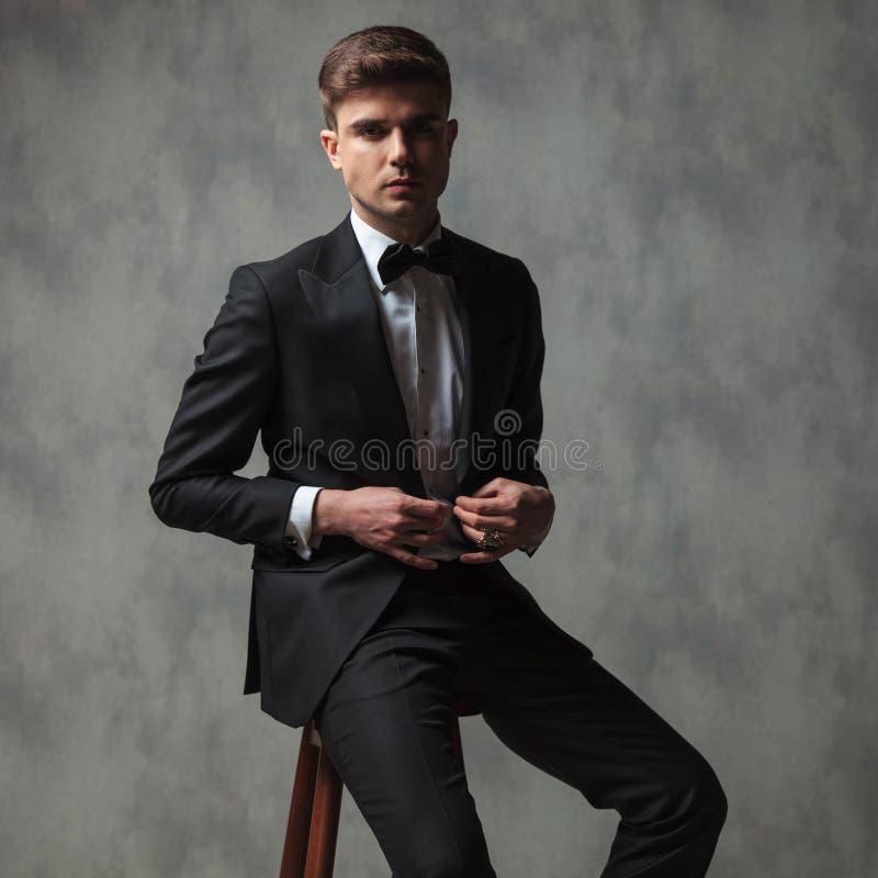 Сексуальный бизнесмен одел официально застегивать его костюм пока sitti стоковое фото