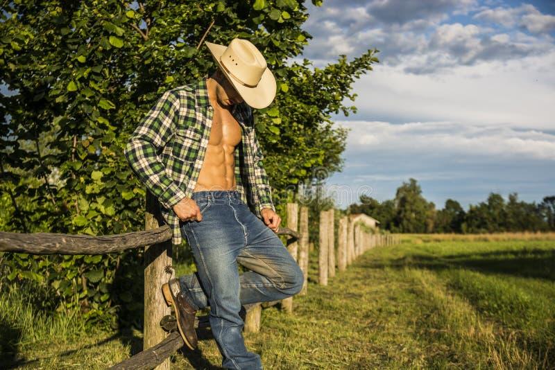 Сексуальный фермер или ковбой с unbuttoned рубашкой стоковое фото