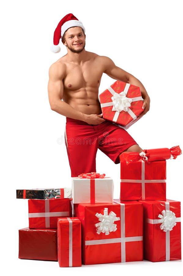 Сексуальный человек Санта Клауса с кучей настоящих моментов стоковая фотография
