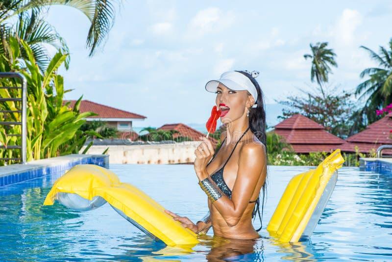 Сексуальная дама с длинными ногами на бассейне стоковое изображение