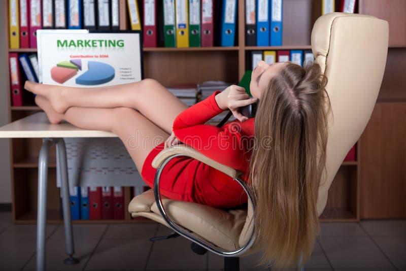 Сексуальная бизнес-леди говоря на телефоне на офисе стоковые изображения