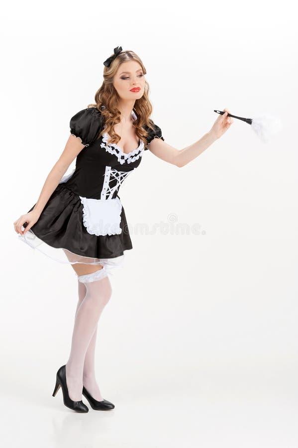 Сексуальная горничная. Красивая молодая горничная в белой щетке удерживания колготки стоковое фото rf