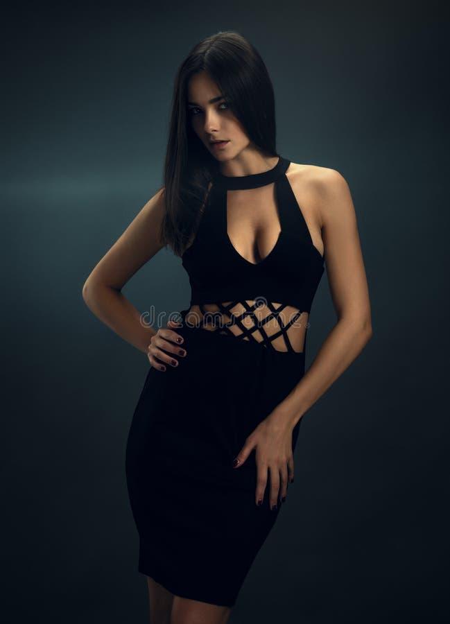 Сексуальная девушка в черном кож-плотном платье стоковое изображение rf
