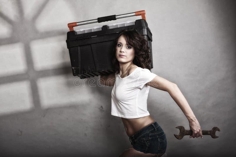 Сексуальная девушка держа гаечный ключ toolbox и ключа стоковое фото rf