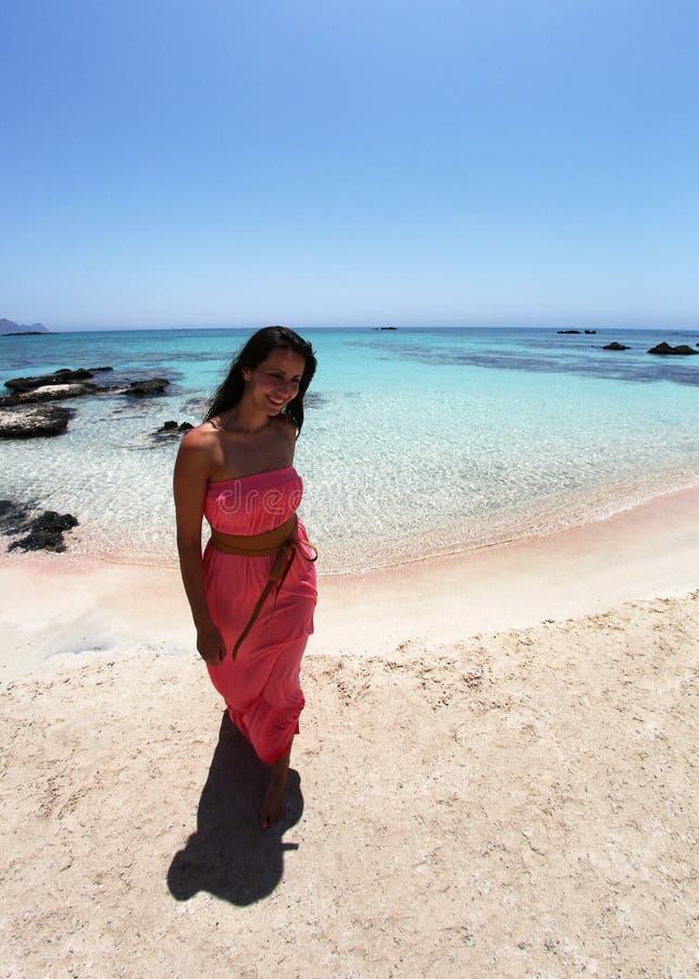 Сексуальная девушка идя на пляж в платье коралла стоковые изображения rf