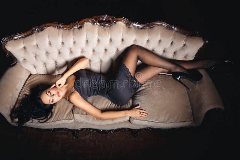 Сексуальная девушка на кресле в черном платье стоковая фотография