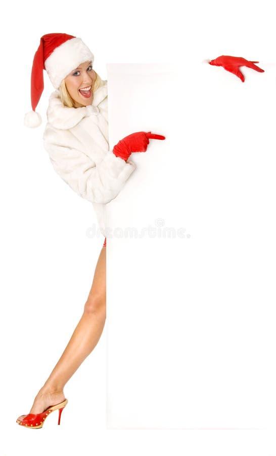 Сексуальная девушка одетая как Санта Клаус указывает палец к космосам экземпляра стоковая фотография rf