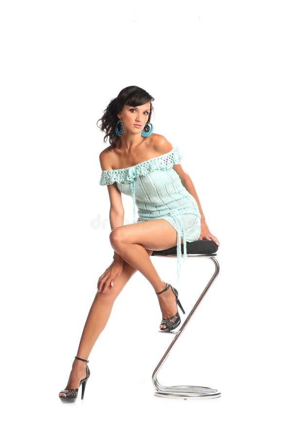 Сексуальная женщина брюнет нося не доходя изолированное платье сидит на табуретке на белой предпосылке портрет тела полный стоковые фотографии rf